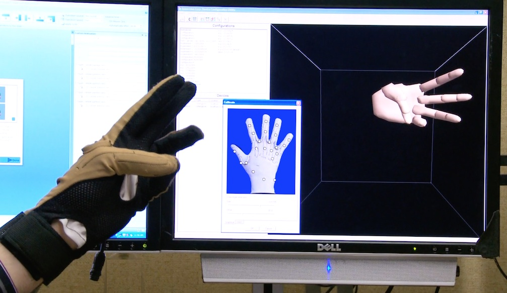 Cyberglove in front of computer screen showing the hand shape.